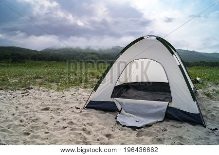 tourist tent on the sandy shore on a cloudy day