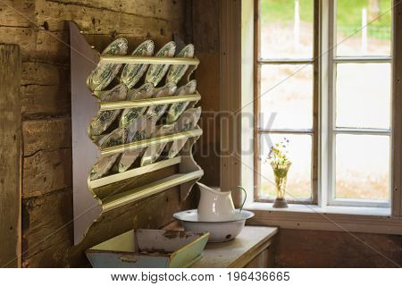Retro decorations concept. Vintage shelf with decorative plates hanging next to window in old cottage