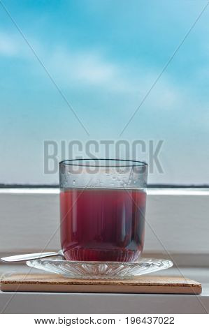 Black hot tea steaming in a vintage glass on cork pad on windowsill. Vertical orientation. Blue sky.