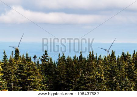 Far away wind turbines with vibrant trees during a beautiful cloudy day. Quebec, Canada.