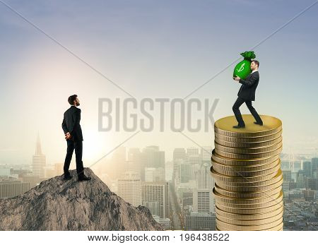 Businessman on mountain top looking at colleague standing on golden coins with money sack in hands. City background. Wealth income and finance concept. 3D Rendering