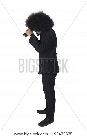 Side view of Afro businessman looking through a binoculars and standing in the studio