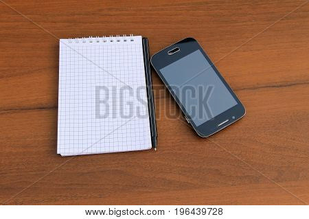 Notepad With Pen And Smartphone On Wooden Desk