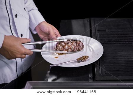 Closeup of a male chef cooking and seasoning beef steak on the grill