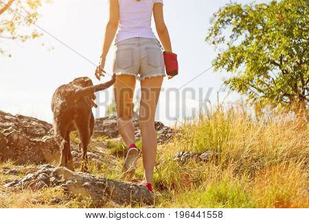 Young woman with her dog walking outdoor during summer day.