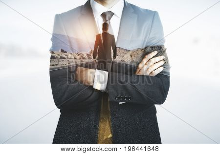 Young businessman with folded arms thinking about way to success. Future concept. Double exposure