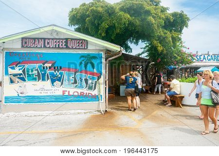 Key West , Florida, USA - June 26, 2012; Large cafe sign with greetings from Key West message and tourists walking by