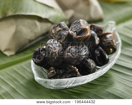 bowl of the dates on the banana leaf