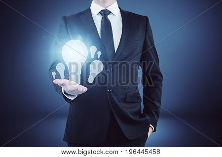 Businessman holding glowing lamps in abstract gradient interior. Idea and enlightenment concept