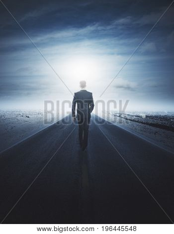 Back view of young businessman walking on road. Future concept