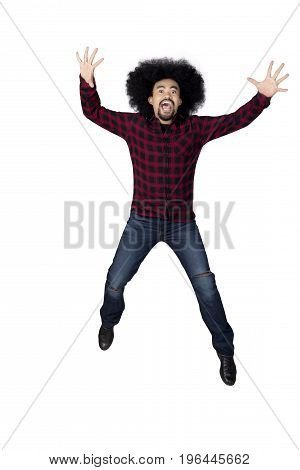 Portrait of happy African person with curly hair leaping in the studio. Isolated on white background