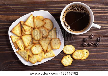 Cup of hot coffee and crackers with cheese flavor on wooden table top view