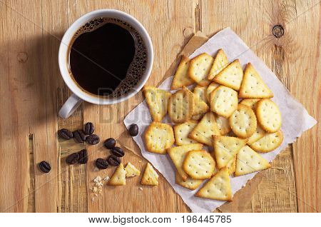 Cup of hot coffee and crackers with cheese flavor on old wooden table top view
