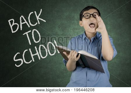 Portrait of little boy screaming while holding a book with back to school text on the chalkboard in classroom
