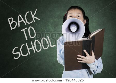 Little girl speaking on megaphone while holding a book with back to school word on chalkboard in the classroom
