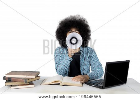 Image of a male college student is yelling by using a megaphone while studying with a laptop and textbooks on the desk