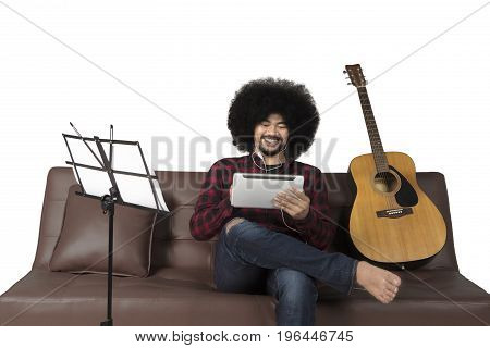 Afro man using digital tablet and listening a music while sitting on couch isolated on white background