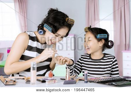 Image of young mother doing makeup while painting nails her daughter and sitting in the bedroom