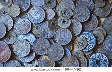 Numismatic collection of old coins from various years asian countries on a table background photo