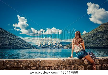 Beautiful Young Woman Looking And Waiting For Amazing White Sailboat At The Seacoast. Montenegro, Eu