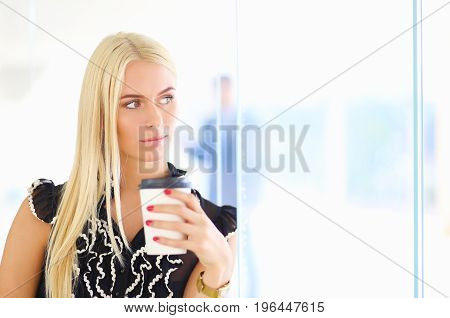 Businesswoman holding a cup of coffee standing in office