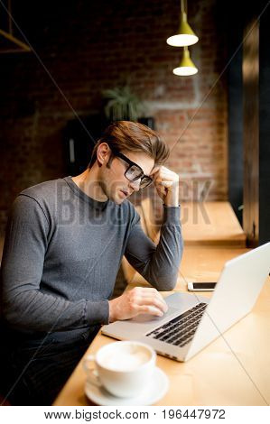 Confused With Hands On Head Young Freelancer In Front Of A Laptop