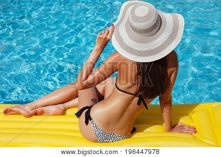 Portrait Of Beautiful Tanned Woman Relaxing In Bikini And Hat In Swimming Pool. Gel Polish Red Manic