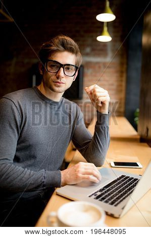 Handsome Worker In Glasses Drinking Coffee While Watching Video On His Laptop At Office