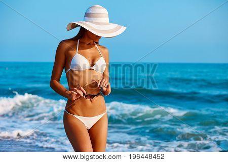 Portrait Of Sexy Beautiful Tanned Woman Posing In Colorful Swimwear Bikini At The Sea Coast. Exotic
