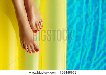 Portrait Of Beautiful Tanned Woman Relaxing In Swimming Pool. Yellow Inflatable Matress. Legs Close