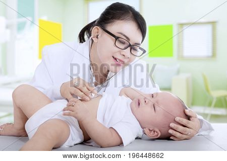 Portrait of beautiful pediatrician examining a little baby with stethoscope in the hospital