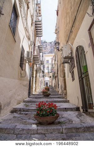 A narrow street in Cefalu Sicily - Italy. Washing and awnings hang from the balconies of buildings