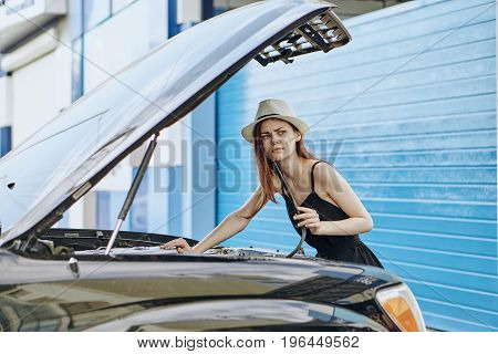 Young beautiful woman trying to fix a car on the street.