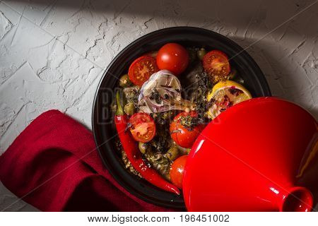 Red tazhin with vegetables, napkin on white background horizontal