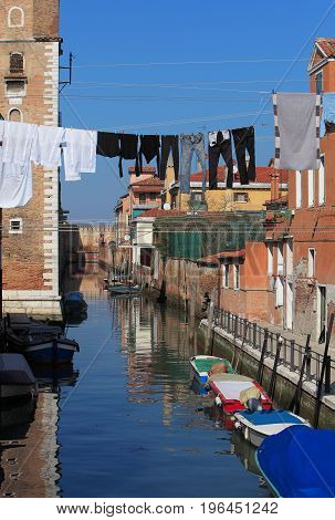 Specific canal with parked boatsspecific architecture and clothes hanging out to dry in VeniceItaly.