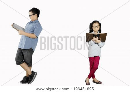 Image of two children reading a book while learning together with a book in the studio isolated on white background