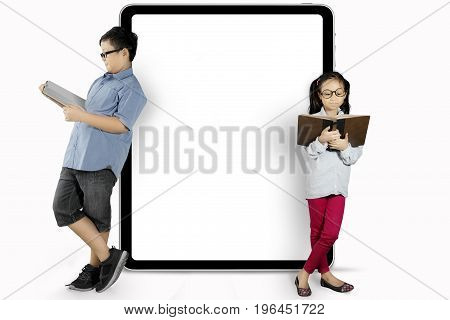 Two children leaning on a blank chalkboard while reading a book in the studio isolated on white background