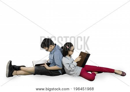 Two elementary students reading a book while sitting in the studio isolated on white background