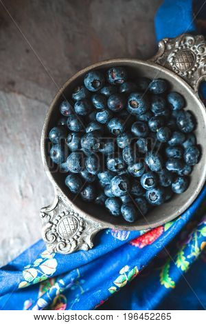 Tin bowl with blueberries, colored napkin on slate copy space vertical