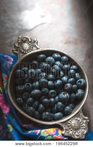 Blueberries in a tin bowl and napkin on slate vertical