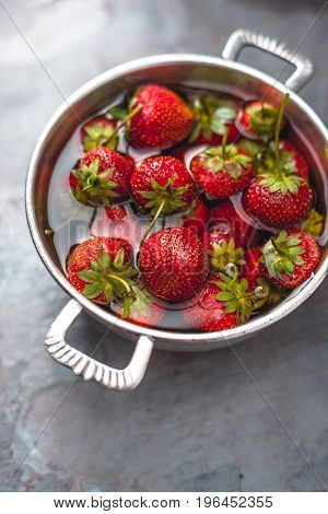 Fresh strawberries in a bowl on table copy space vertical