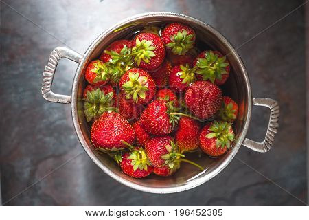 Strawberries in a tin bowl in the center of the table horizontal