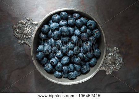 Berry bilberry in a tin bowl on a gray slate closeup horizontal