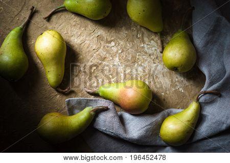 Ripe pears, gray napkin on a green table horizontal