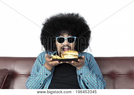 Portrait of young man eating hamburger and french fries while sitting on sofa