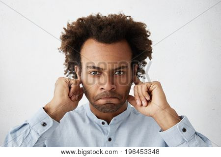 Angry Annoyed Bearded Young African Man With Compressed Lips Dressed In Light-blue Shirt Plugging Ea