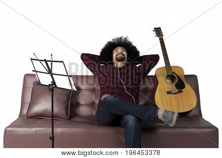 Young man enjoying music with earphone while sitting on couch isolated on white background