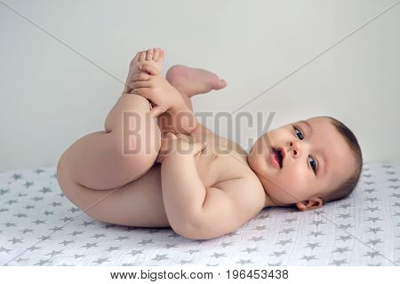 naked baby lying on his back on the diaper