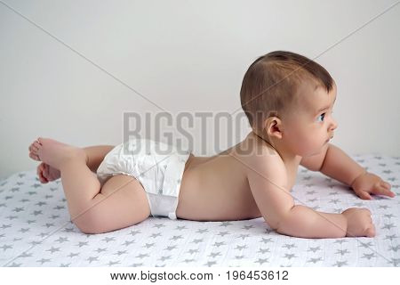 naked baby in diapers lying on her belly on the diaper with stars