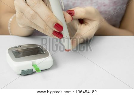 Hands of young woman using a lancet while examining blood sugar with a glucometer